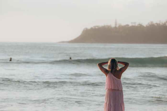 female in pink dress standing near sea in sunny day